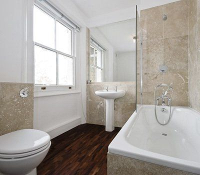 White bathroom suite on a timber floor, and marble effect wall tiles