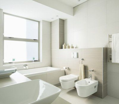 Cream and white bathroom with bidet and double washbasin