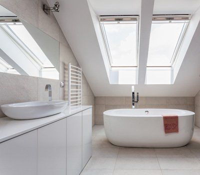 Oval bath underneath a skylight window, against a wall with a white towel rail