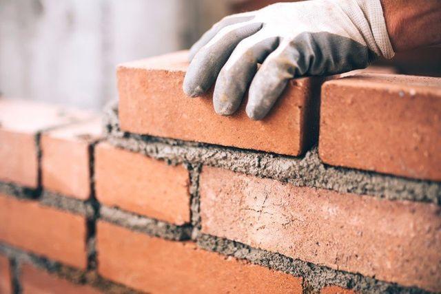 una mano che pone un mattone su del cemento fresco