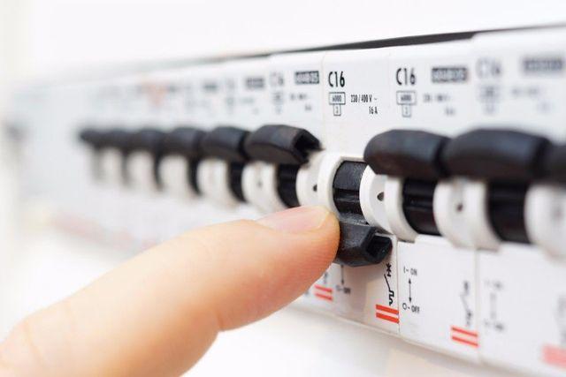 Un dito che spegne un interruttore di un quadro elettrico