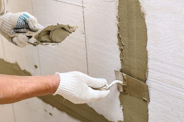 Una mano con del cemento fresco e un'altra che lo spalma con una spatola