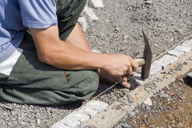 Man paving a retaining wall in Whangari