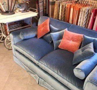 un divano grigio con cuscini arancioni