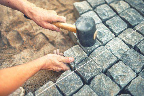 primo piano di mani che costruiscono un pavimento a mosaico in porfido