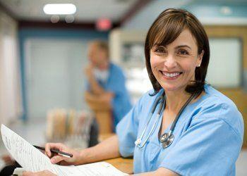 una dottoressa con un camice azzurro e uno stetoscopio
