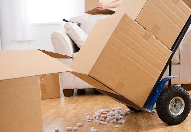 Varie scatole di cartone da imballaggio e carrello traslochi