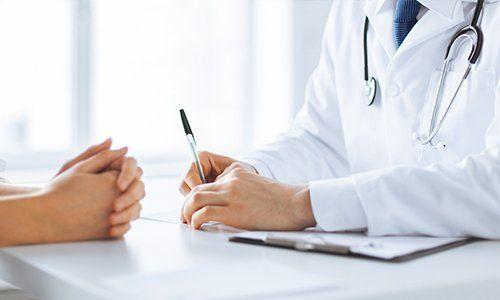 due mani di un medico appoggiate sulla scrivania con una penna