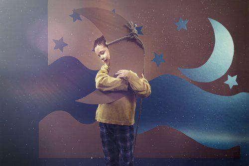 bambino durante una rappresentazione teatrale abbraccia una luna fatta di carta