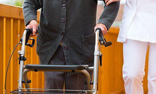 vista di una persona che indossa un cappotto nero mentre cammina con un deambulatore e sulla destra una donna con un camice bianco