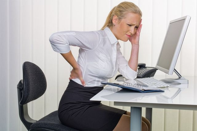 Lady sitting at her desk in pain holding her lower back and head