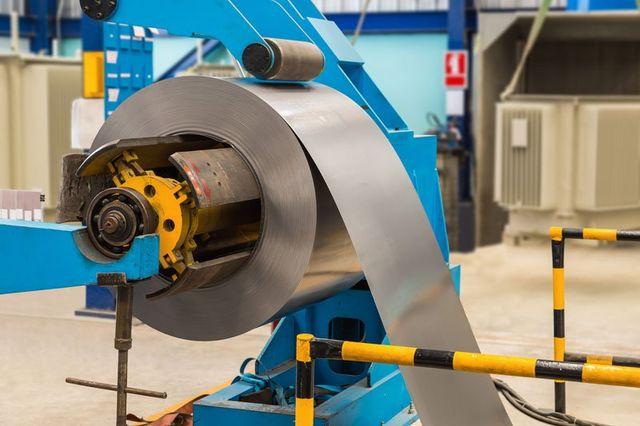 un macchinario industriale di color blu e giallo con un rotolo grande di fogli di alluminio
