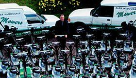 The owner of Alex McDougall (Mowers) Ltd surrounded by mowers