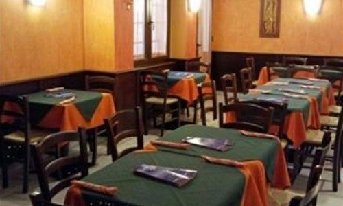 tavoli all'interno del ristorante con tovaglie arancioni e centrini verdi