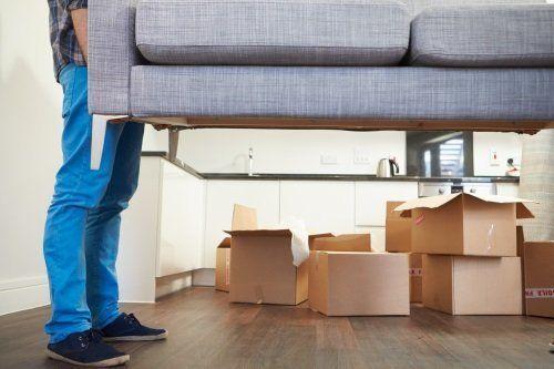 Due operatori caricando un sofà in una stanza piena di casse