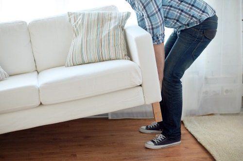 Uomo alzando un sofà