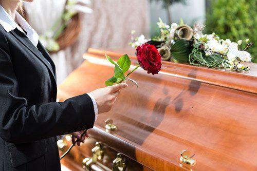 persona mette una rosa sulla bara durante un funerale