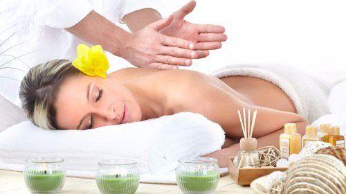 Bella giovane ragazza, sdraiata si gode un massaggio rilassante in un spa