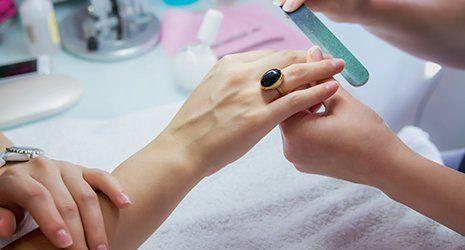 mani donna in un salone di bellezza riceve una manicure da un estetista con lima per unghie, nail limatura