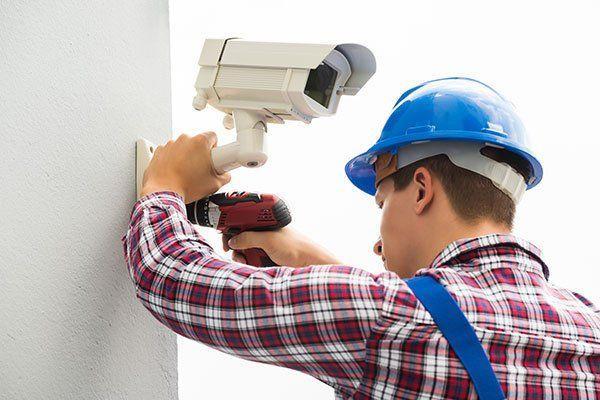Giovane Maschio Tecnico Installazione telecamera sulla parete con cacciavite