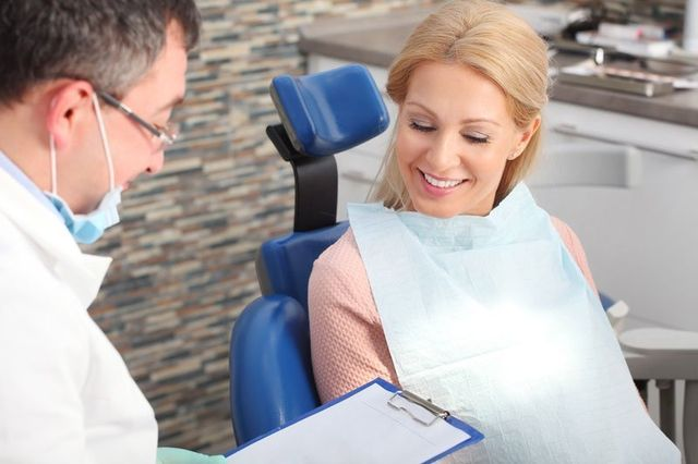 Woman sitting at dentist office and consulting with her male dentist