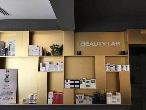 dei prodotti di bellezza in esposizione su delle mensole e la scritta I Beauty Lab