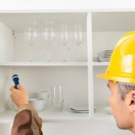 Pest control worker with flashlight checking kitchen shelf