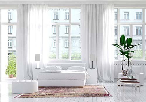 Grandi finestre in colore bianco in una camera da letto