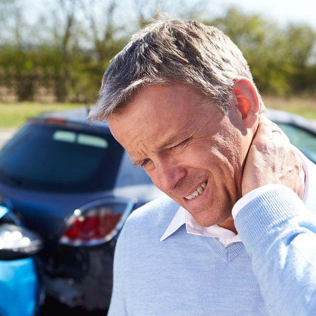 Man gripping his neck in pain as he has a whiplash after a traffic accident