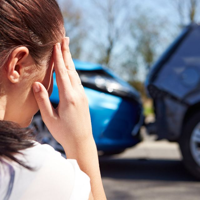 A stressed woman sitting down after a car accident