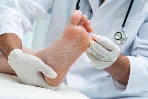 due mani con dei guanti che controllano un piede