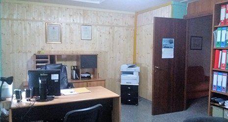 Ufficio con porta aperta, vista  libreria, scrivania con monitor e stampante