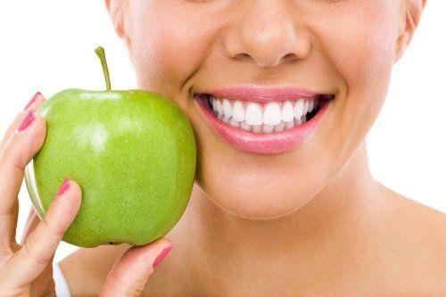il sorriso di una donna con in mano una mela verde