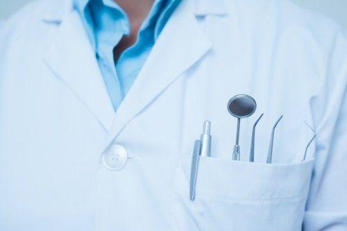 una penna e degli attrezzi dentistici nel taschino di un camice