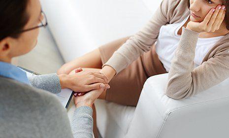 Psicologo che tiene la mano ad una paziente