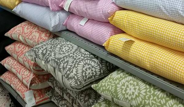 dei cuscini colorati dentro a uno scaffale di ferro