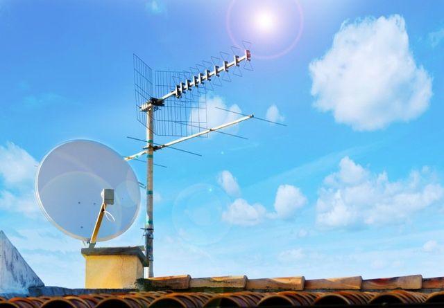 un tecnico che monta una parabola su un tetto