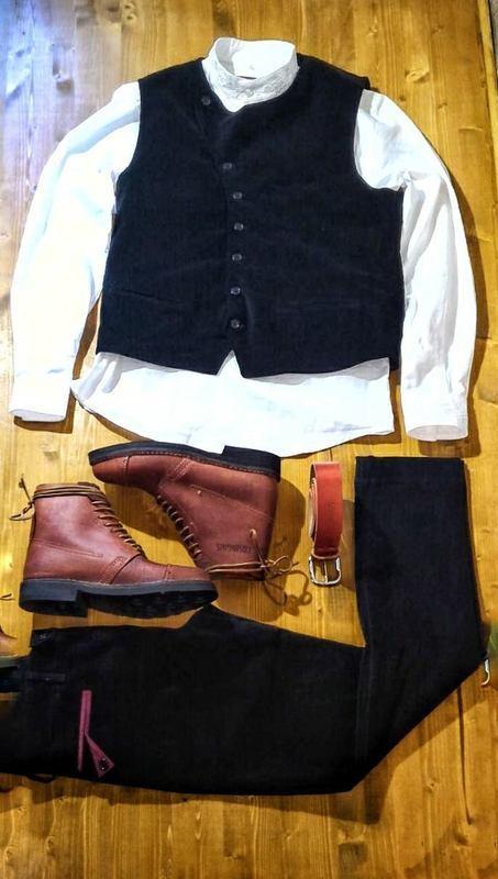 un gilet scuro sopra una camicia bianca degli scarponcini in pelle e una cintura