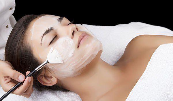 Un tecnico applica una crema antietà sul viso di una donna con un pennellino