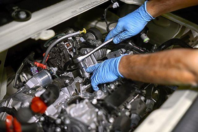 due mani di un meccanico con guanti in lattice azzurri mentre sta avvitando un bullone del motore