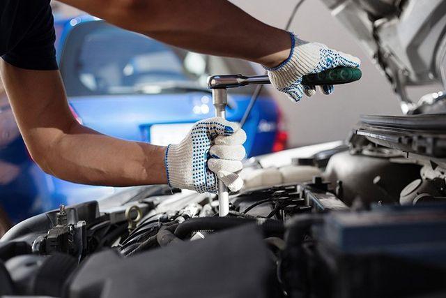 due mani di un meccanico che sta avvitando un bullone con un cacciavite a T nella zona motore di una macchina