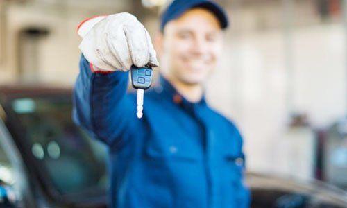 un meccanico che mostra una chiave di una macchina