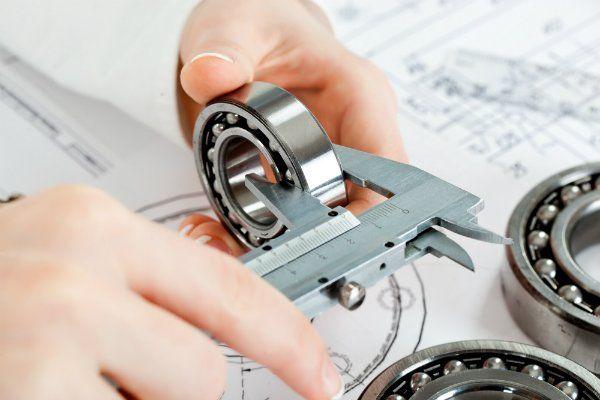 una mano con un calibro che misura un oggetto di ferro