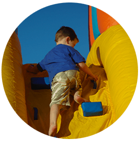 Young kid trying to climb the inflatable castle
