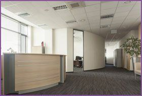 An office reception area with curved pale wood desk, brown laminate floor, cream walls and white suspended ceiling