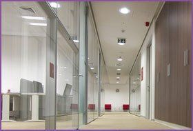 A long office corridor with glass walls
