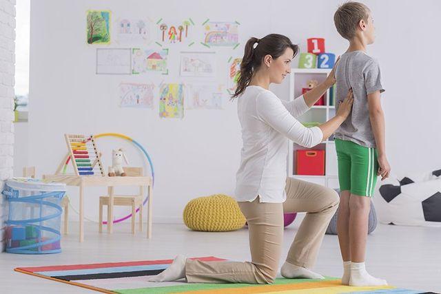 fisioterapista palpa la colonna vertebrale di un bambino in sala riabilitazione
