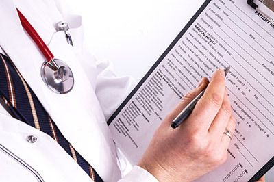 Doctor filling out insurance paperwork