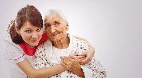 care worker hugging the elderly from behind