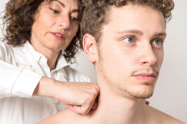 dottoressa con camice bianco pratica fisiokinesiterapia su paziente